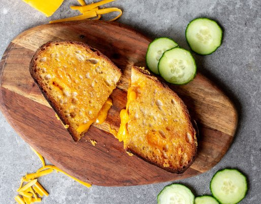 Baked Grilled cheese on wooden board with cucumbers