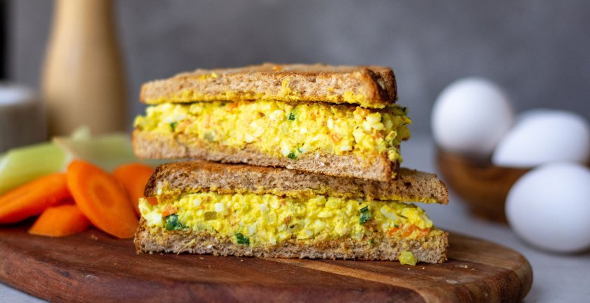 side view of egg salad sandwich on wooden board
