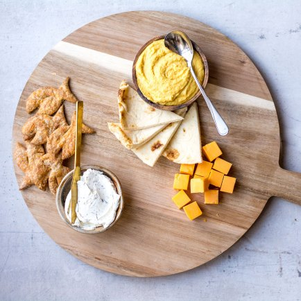 dips and cheese with pita on wooden platter