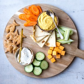 dips and cheese with pita on wooden platter with veggies
