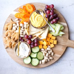 dips and cheese with pita on wooden platter with veggies and fruit