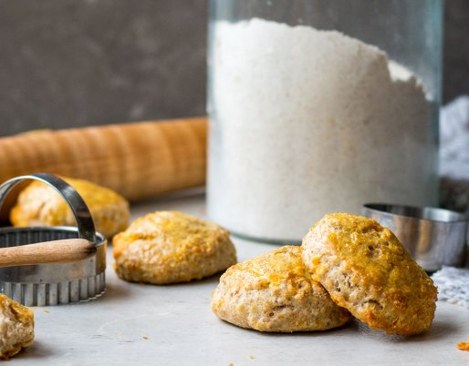 buttermilk biscuits stacked with cutter and flour in background