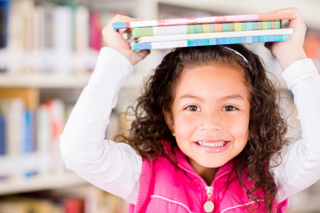 happy-girl-at-the-library-holding-books