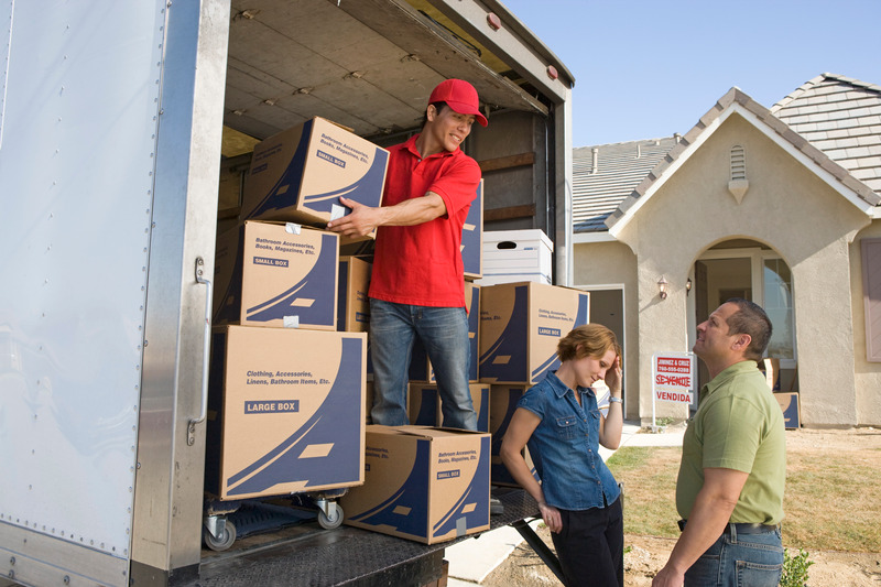 man-and-couple-unloading-truck-of-cardboard-boxes