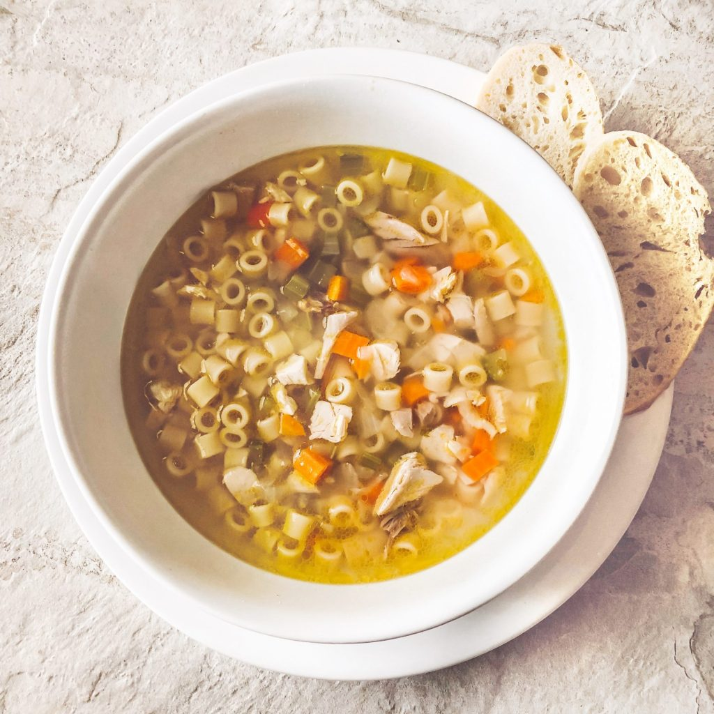 homemade-chicken-noodle-soup-in-white-bowl-with-side-bread