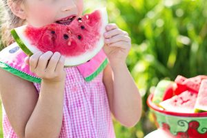 girl eating sliced watermelon beside table