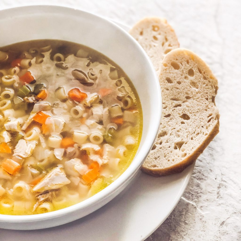 homemade-chicken-noodle-soup-in-white-bowl-side-of-bread