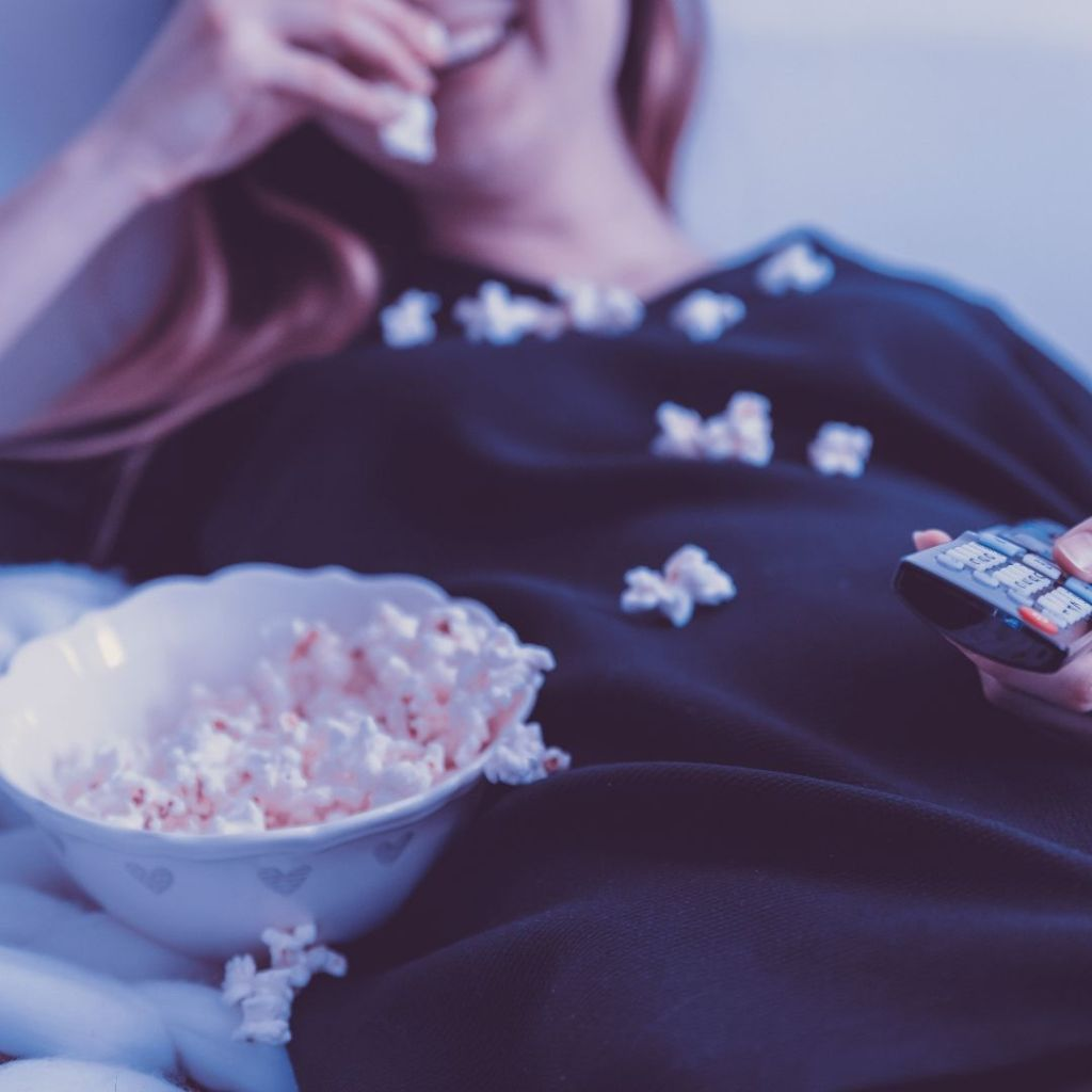 mom on couch watching tv show with bowl of popcorn on her lap