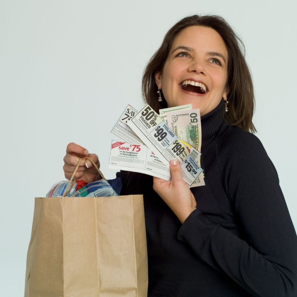 mom-holding-coupons-and-money-with-bag-of-items
