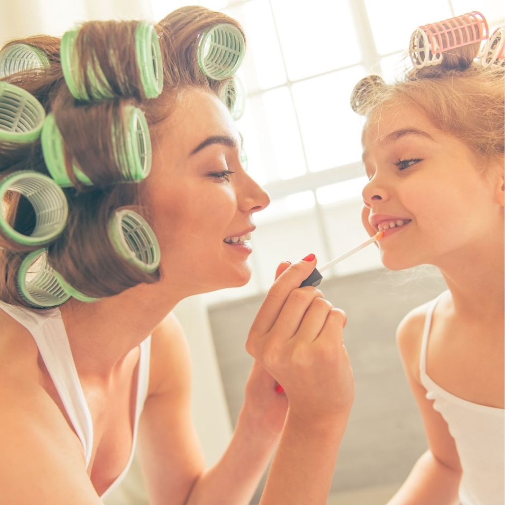 mom-and-daughter-in-hair-rollers-putting-on-lipstick