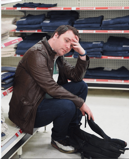 Andrew sitting on a low shelf resting out shopping, head in hand