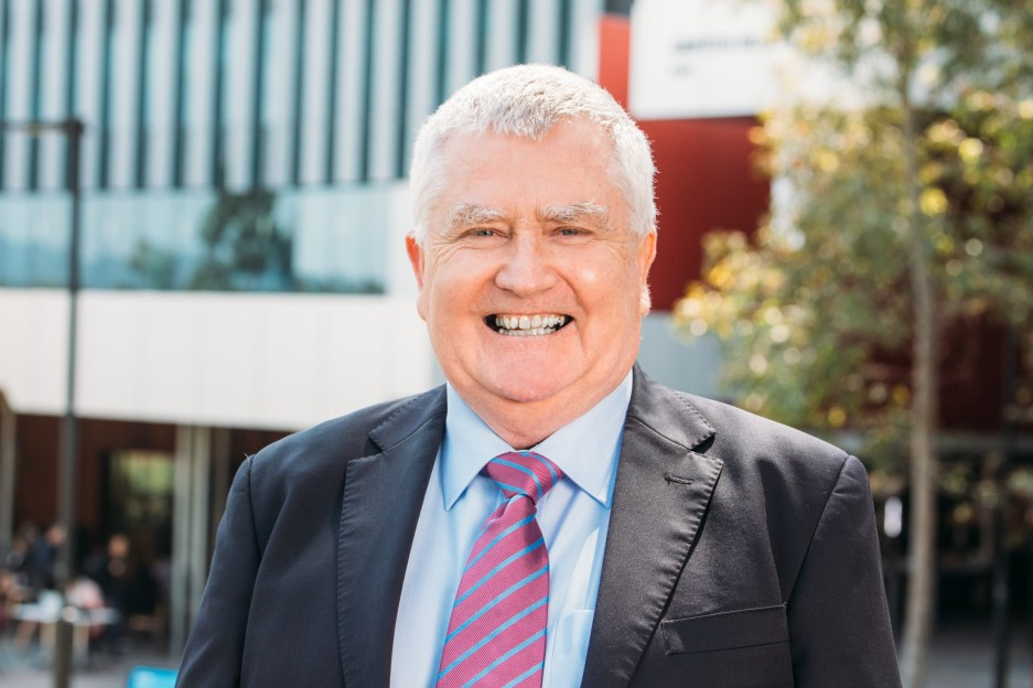 Head shot of Prof Don Staines in suit and striped tie, smiling and standing in front of a Griffith Uni building