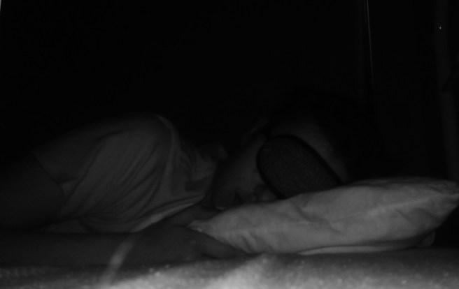 young girl in eye mask lying in darkened room
