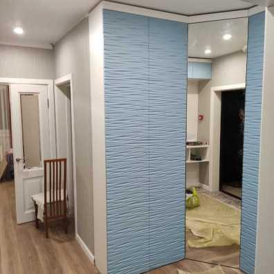 Угловой распашной шкаф с фрезерованными фасадами в виде волны голубого оттенка.