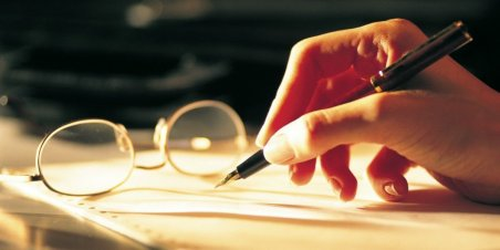 Elinde kalemiyle düşüncelerini yazan bir kimse