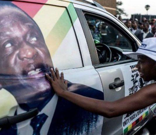 Warga Zimbabwe pendukung pemerintahan baru menyentuh gambar calon presiden baru Emmerson Dambudzo Mnangagwa.(MARCO LONGARI / AFP)