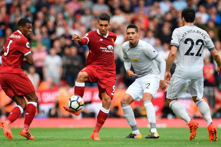 Disaksikan Georgionio Wijnaldum, Roberto Firmino mencoba melewat penjagaan Henrikh Mkhitaryan dan Chris Smalling saat Liverpool menjamu Manchester United di Anfield, Sabtu (14/10/2017).(AFP/Paul Ellis)