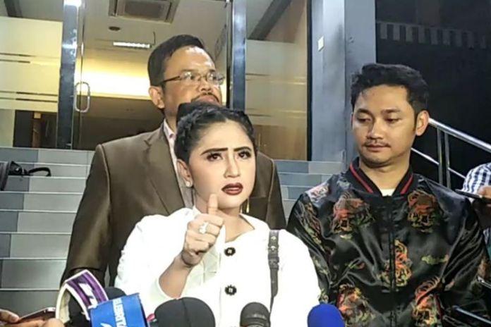 Dewi Perssik (kiri) mendampingi suaminya Angga Wijara (kanan) melaporkan seorang petugas Transjakarta ke Sentra Pengaduan Kepolisian Terpadu (SPKT) Polda Metro Jaya, Senin (4/12/2017) malam.(KOMPAS.com/ANDI MUTTYA KETENG)