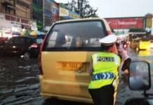 Polisi lalu lintas mendorong angkot yang mogok karena melewati banjir di Jalan Gatot Subroto persis di seputaran Plaza Medan Fair, Jumat (1/12/2017)