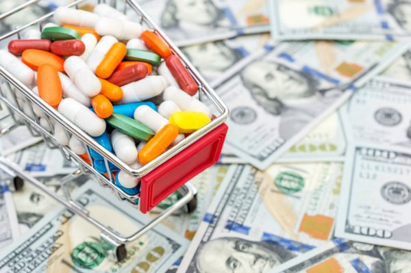 Full shopping cart with pills on background of dollar bills. Close up. Space for text.