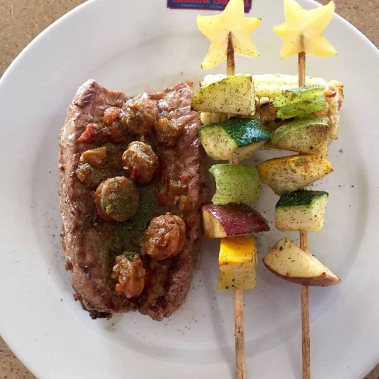 Sirloin steak and pork sausage, with roasted corn and skewers of vegetables and fruits, photo courtesy of Mama Santa