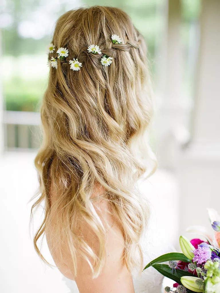 long waves with a waterfall braid and oxeye daisies loose waves wedding hairstyle with flowers
