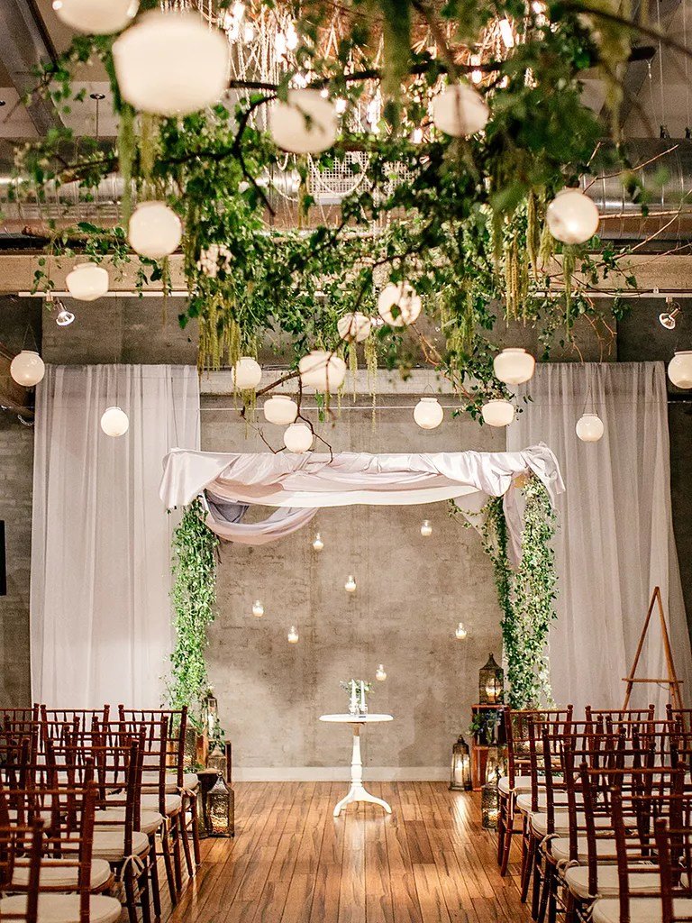 matching hanging lanterns and greenery aisle and arch decor