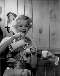 Pevely Dairy model pouring milk into shot glasses. Photograph by Russell Froelich, 1930s. Missouri History Museum