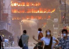 witnesses watch flames spew from one of the several buildings -- in addition to the Twin Towers -- damaged or destroyed in lower Manhattan