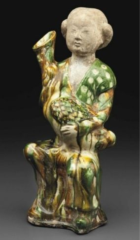 A sancai- glazed figure of a woman holding a goose, Tang dynasty (AD 618-907)