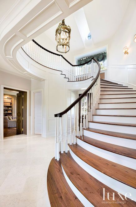 A grand staircase in the foyer sets an Old World tone, ascending in a graceful curve toward the second floor.