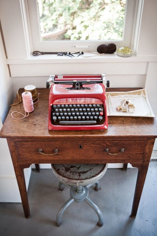 wooden desk with metal stool and red typewriter