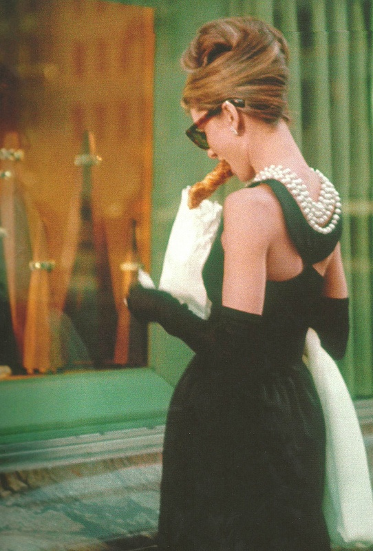 """Audrey Hepburn in """"Breakfast At Tiffany's"""", 1961.  She did not want to eat a danish in this scene; instead she wanted to hold an ice cream cone.  The danish """"won"""" since she was supposed to be having *Breakfast* at Tiffanys."""