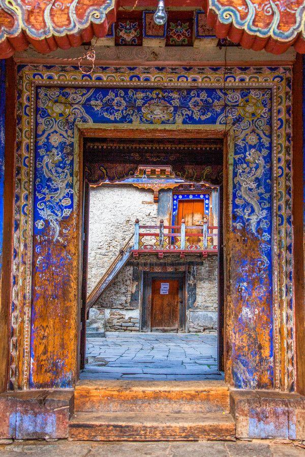 Vista attraverso blu e bianco portale decorato, vecchio tempio Bhutan, mostrando opere d'arte, cortile in pietra, scale e altre porte.  *