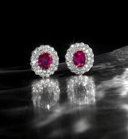 A pair of ruby and diamond cluster earrings The oval-cut rubies, weighing 3.89 and 3.67 carats, each within a double surround of brilliant-cut diamonds, diamonds approximately 2.50 carats total, length 1.8cm