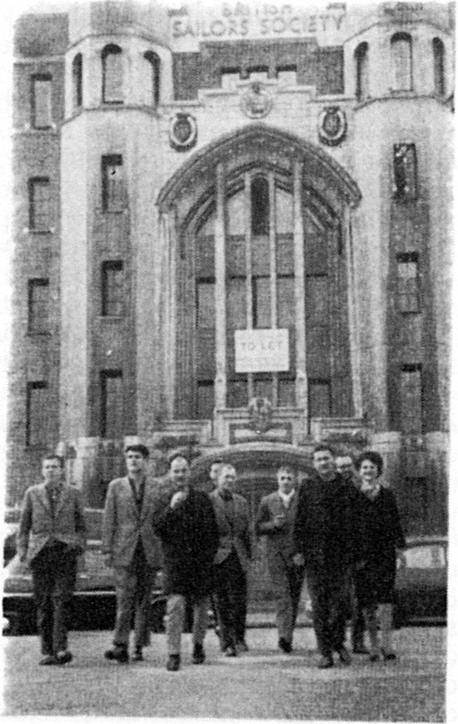 "Situationists at the Sailors' Society in London during the 4th Conference of the Situationist International. Those assembled included (from l. to r.): Attila Kotányi, Hans-Peter Zimmer, Heimrad Prem, Asger Jorn (covered), Jørgen Nash (front), Maurice Wyckaert, Guy Debord, Helmut Sturm, and Jacqueline de Jong. To ensure that the proceedings were kept away from any contact with artistic circles or London newspapers, the conference took place in Limehouse, ""a district renowned for its criminals."""