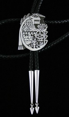 Chalmers Day Shaman Kachina Overlay Bolo Tie | eBay http://ow.ly/oIBj8 Precision Hopi silversmith Chalmers Day has created this stunning bolo tie using his incredibly fine cutout work and overlay technique. The bolo features the shaman kachina holding a basket of corn representing abundance. Below him are the rain, sun face and weather symbols necessary for growth of the crops. The butterfly maiden makes an offering in prayer for rain as the mudhead rises from the underworld to greet her.