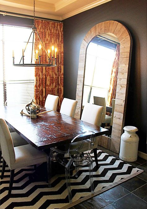 Charcoal walls, chevron rug, leaning wall mirror and wooden table. Nice mix of modern, rustic, artsy style. Dining room inspiration.