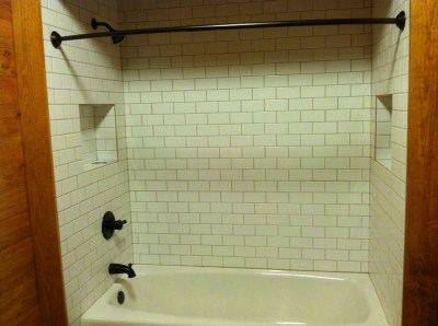 "New shower with 3""x6"" subway tile over 66"" cast iron tub with two soap/shampoo niches."