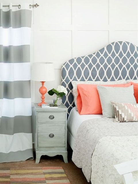 A patterned, fabric covered headboard says style against white walls. Wide striped draperies infuse the room with another layer of pattern, but they don't steal attention away from the headboard. Coral accents throughout the space provide warmth and color. Smaller scale patterns on the bedding and solid pillows complete the room's pattern mix.