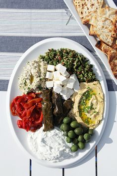 Mezze Platter With Grilled Pita A mezze platter, filled with hummus, tzatziki, tabbouleh, and more, staves off hunger and can withstand outdoor temperatures for several hours (