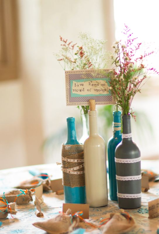 Theresa - painted bottles with embellishments? I like the one bottle with a cork in it to stick a table number or something.