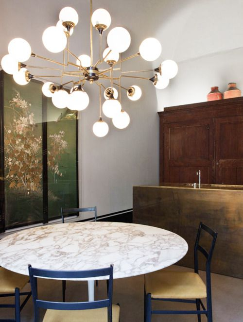 lamp, saarinen table, gio pionti chairs and bronze kitchen island