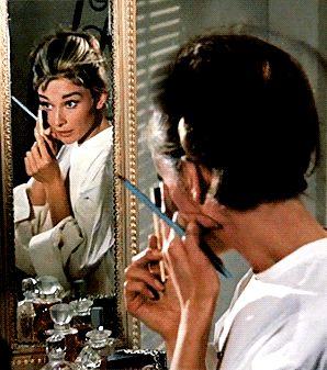 Audrey Hepburn doing her makeup