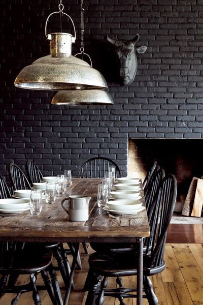 Dark dining space with farm-style wooden dining table.