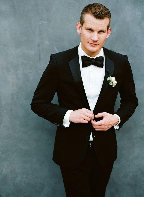 groom in black suit and black bow tie...