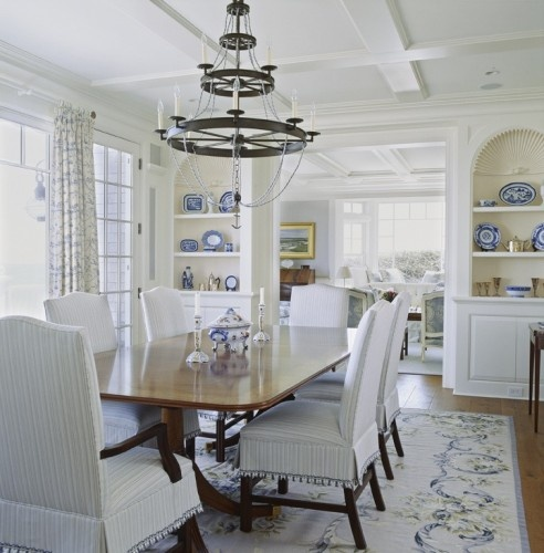 Cream and blue needlepoint rug in dining room with soothing pale blues and lovely chandelier