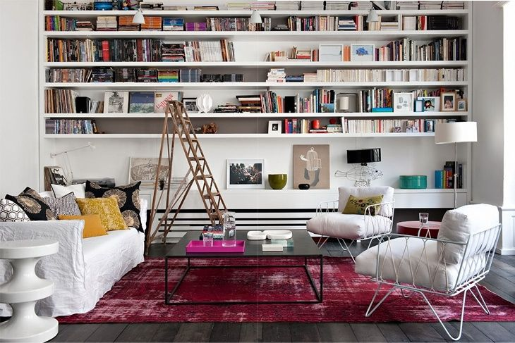 eclectic modern apartment in Paris with white linen upholstery, an overdyed rug, a rustic ladder, and a wall of bookshelves // living rooms