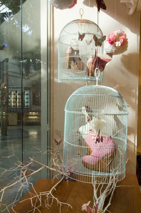 I love the vintage bird cages being used to display merchandise! Looks very pretty, with just a touch of antiquity!