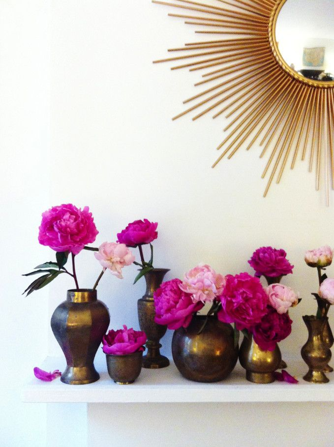 Lonny market editor Cat Dash arranges pink peonies in vintage brass vessels on her mantel.  How do you love to display fresh blooms?